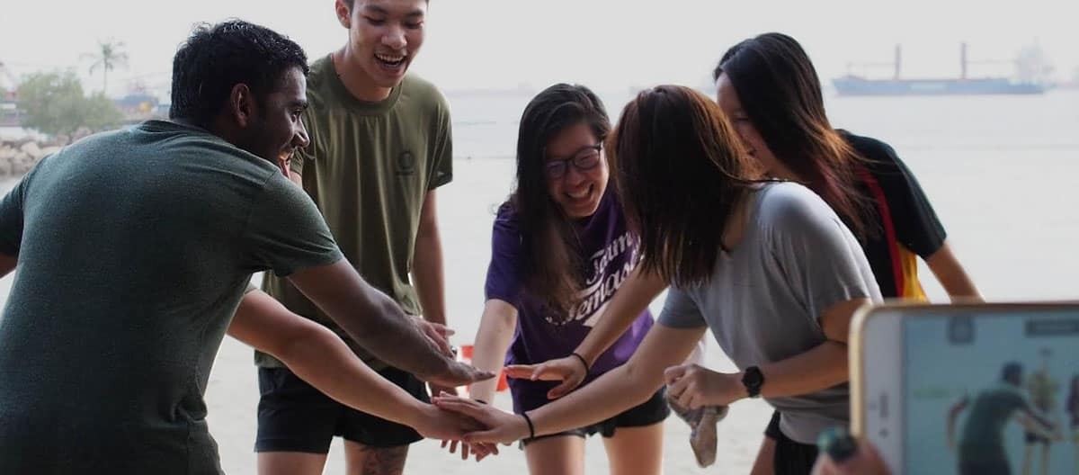 Embry-Riiddle Asia students hands all in on a beach